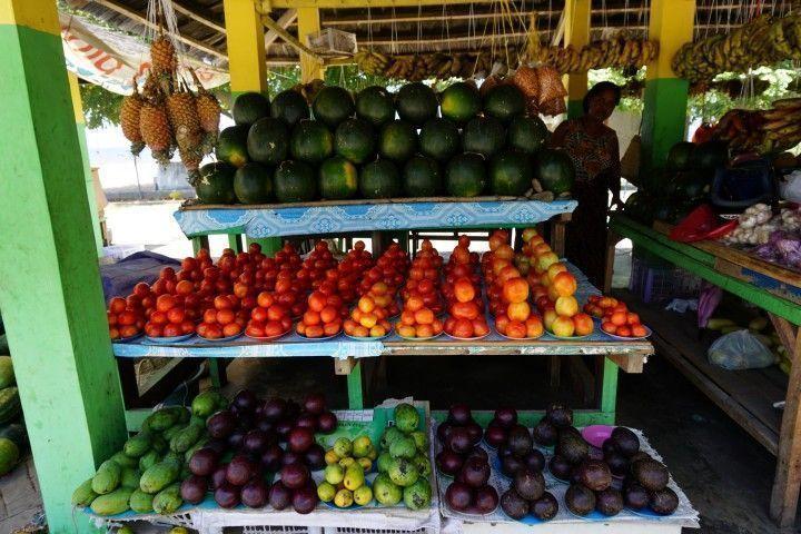 Puesto del mercado de frutas y verduras con sus perfectas pirámides de tomates