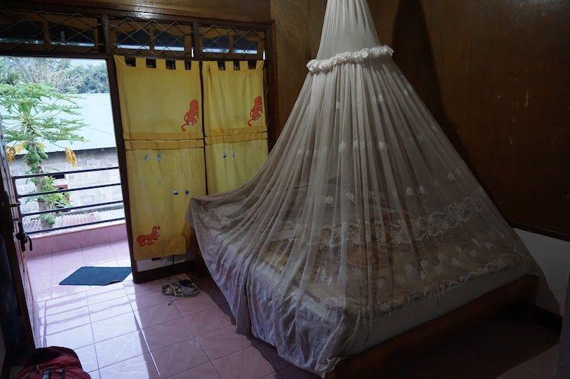 cama con mosquitera en watugana bungalow en moni