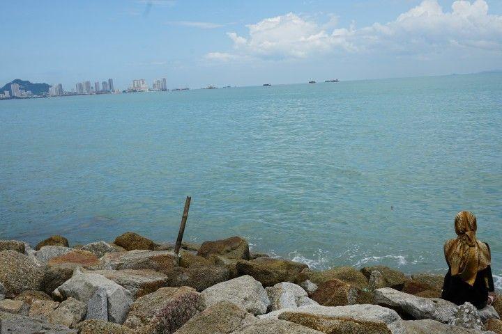 Una mujer con la mirada perdida a orillas del estrecho de Malaca, en George Town