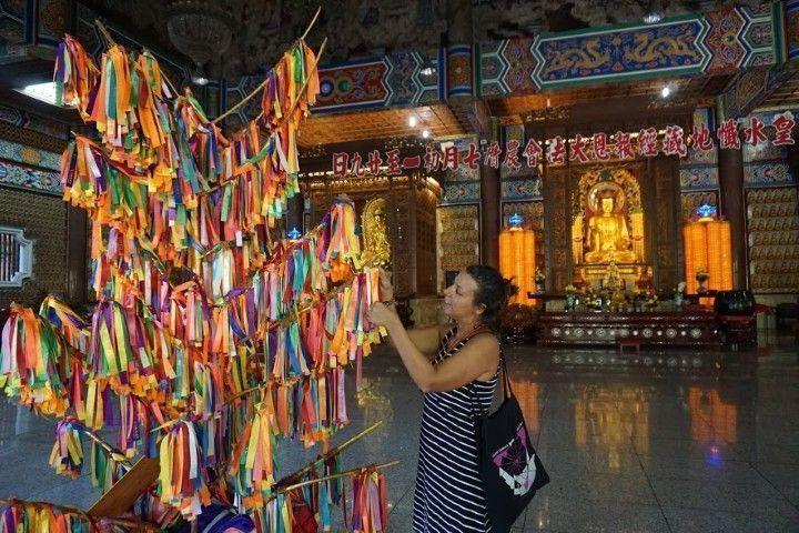 Inês pidiendo un deseo, atando al árbol la tira correspondiente al deseo pedido. Cada deseo tiene una tira de color distinto.