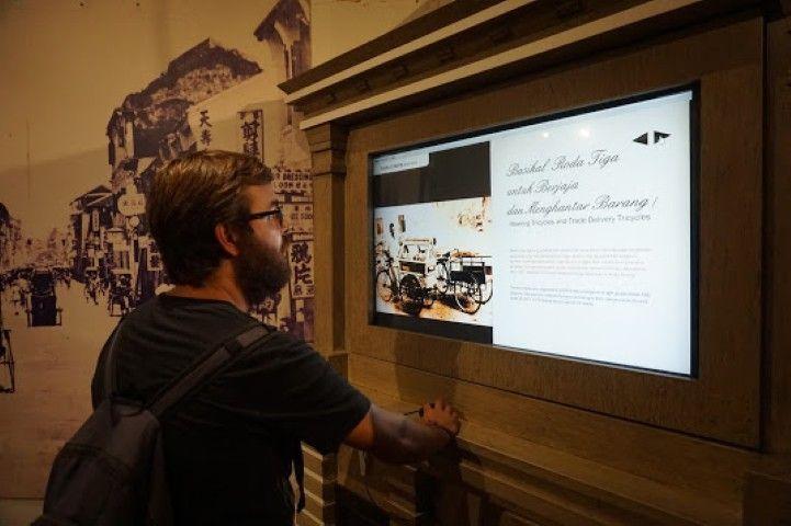 Chris aprendiendo sobre como surgieron los trishaws en Penang, con un panel interactivo del Museo