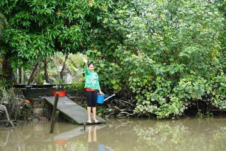Una chica nos saluda a nuestro paso por delante de su casa en el Delta del Mekong