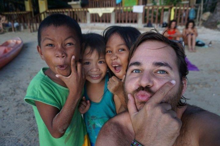 Chris con niños en la playa al lado del bungalow, el Nido.