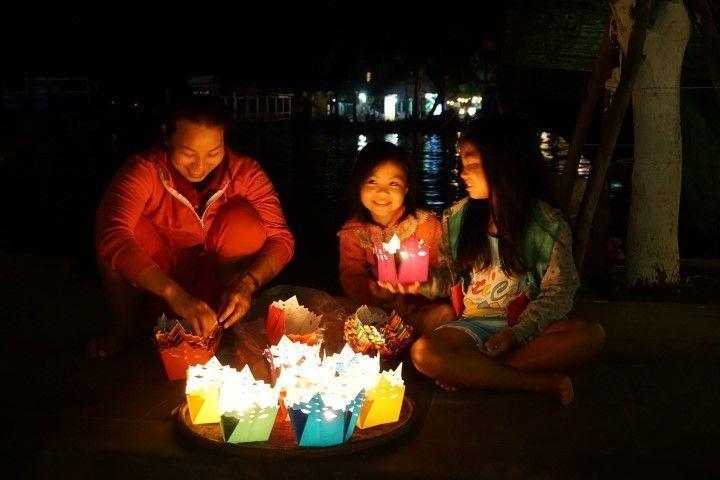 Niñas y su madre, vendiendo las flores de loto de cartón con velas para pedir deseos a Lady Buddha