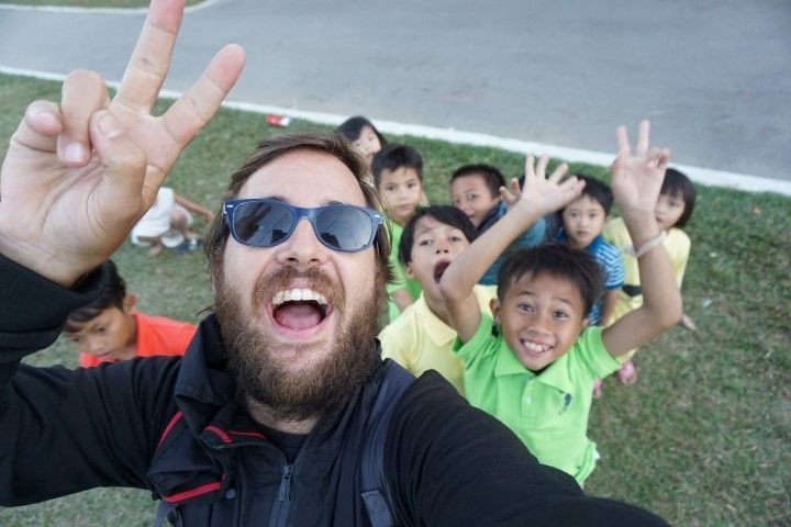 Selfie de Chris con niños, en el jardín frente a la iglesia.
