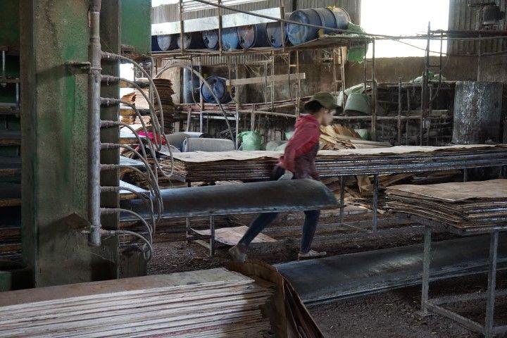 Una de las trabajadoras de la fábrica, cargando una chapa muy pesada de metal.