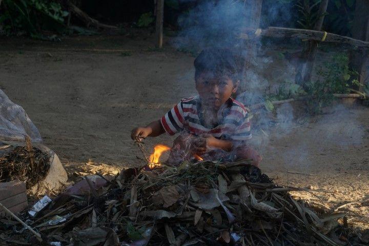 Niño haciendo fuego por la mañana