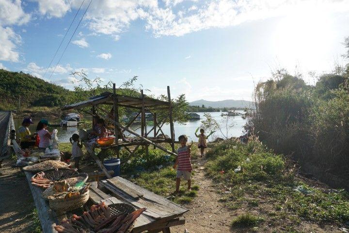 Niños saludando a orillas del río, en su pueblo flotante.