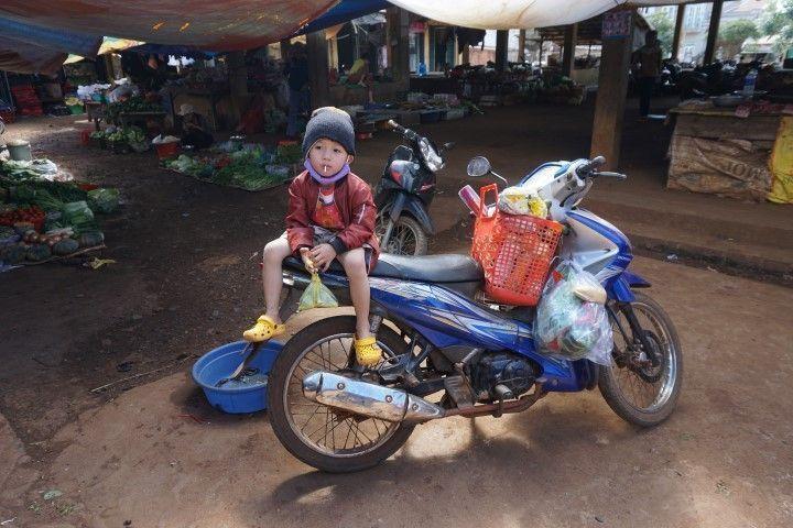 Un niño encima de la moto de su padre en el mercado
