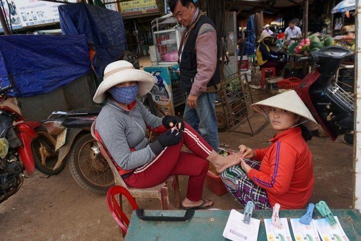 Haciendo la pedicura en el mercado