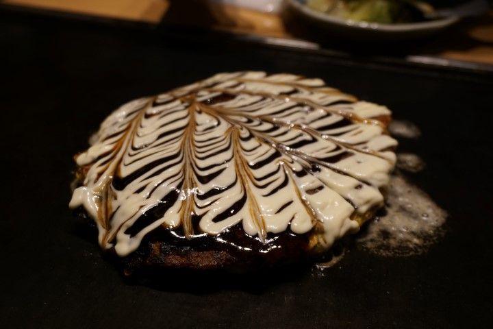 """¡El Okonomiyaki! Sí, tiene nombre raruno y viene básicamente de que """"okonomi"""" significa """"lo que quieras"""" y """"yaki"""" """"a la parrilla"""". Así que consiste en una especie de tortilla con noodles o tiras de col con una gran variedad de ingredientes: verduras, carne, marisco... Cocinado a la plancha (a la vista en nuestro caso) con salsa okonomiyaki y mayonesa por encima. Un plato muy típico de Osaka aunque también nos han dicho que era típico de Hiroshima."""