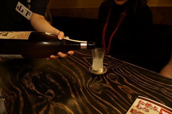Sake :) Las botellas de Sake son más grandes de lo normal, sí. Además el sake se sirve con un platillo debajo del vaso para que cuando el vaso se llena, se desborde el liquido y se quede en el platillo. Supuestamente vas llenando en sake del platillo mientras el vaso se vacía pero esta parte no la tenemos claro.