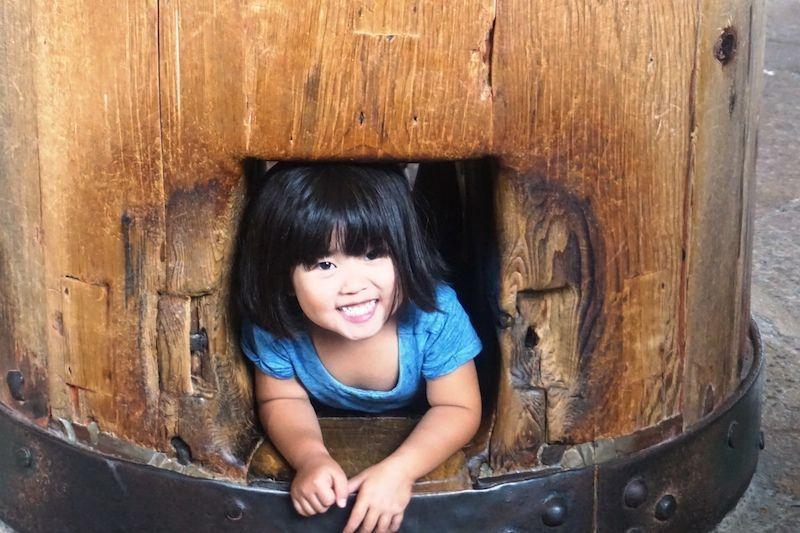 Una niña pasando por la columna del templo Todai-ji