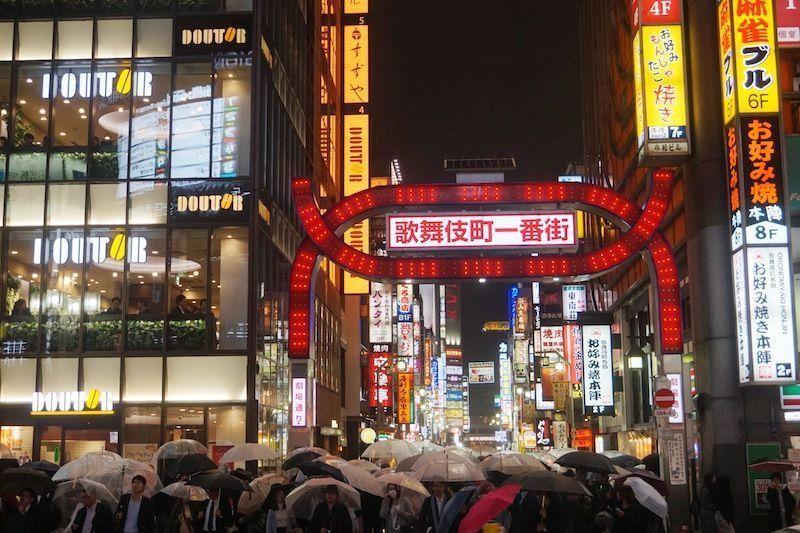 Mucha gente con paraguas en Shinjuku un viernes noche