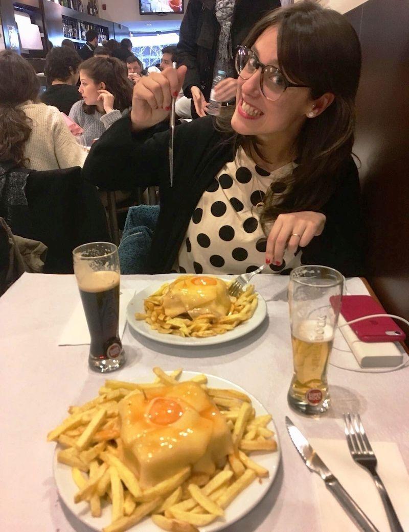 """Ana con su francesinha son la definición gráfica de felicidad a la hora de la comida.""""¡Saca la foto rápido que quiero zamparme a esta maravilla ya!"""" , además en café Santiago tenían cañas (imperiais) de su apreciada cerveza negra (cerveja preta en portugués)."""