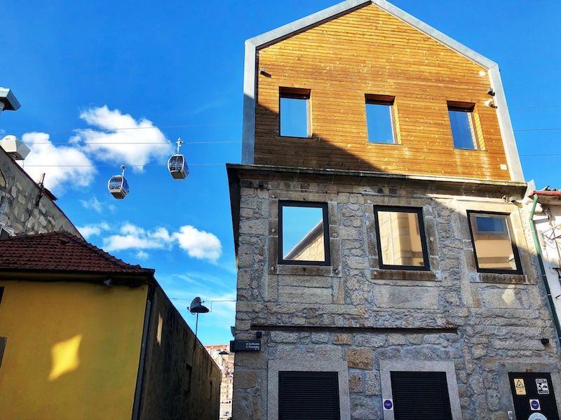 Unos funiculares pasando en una fotogénica fachada soleada...