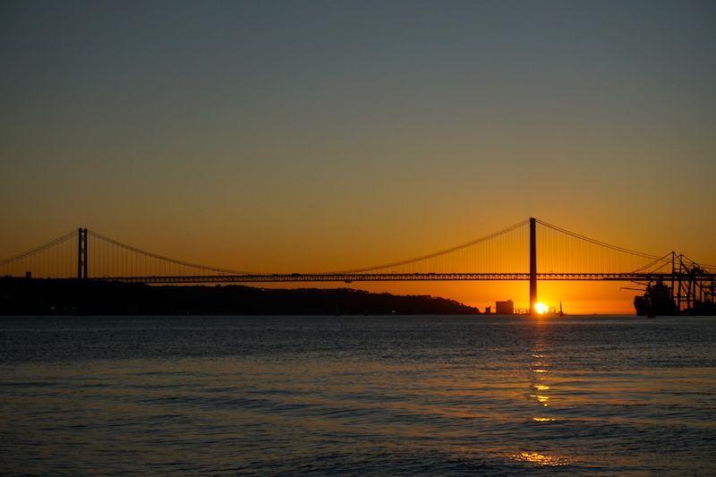 Puesta de sol desde el barco (el cacilheiro) de Lisboa hacia Cacilhas, con el Tajo y el puente 25 de Abril de protagonistas