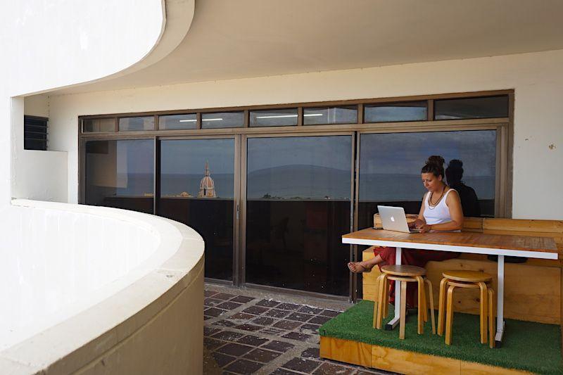 Inês trabajando con vistas en Cartagena de Indias. Con una tarjeta SIM local podrás hacer tethering y compartir internet con tu ordenador portátil