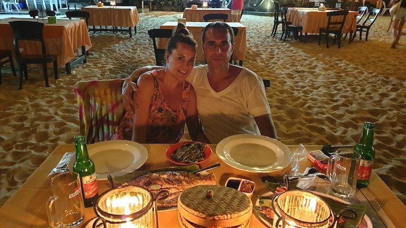 Cena romántica con los pies en la arena y el mar de banda sonora, en Jimbaran