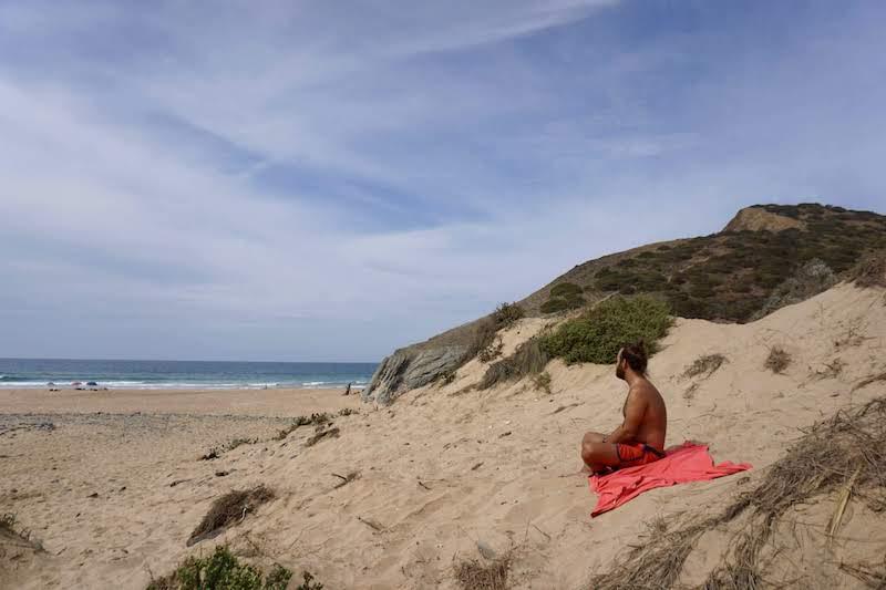 Chris descansando en las dunas con vegetación en Playa de Barriga