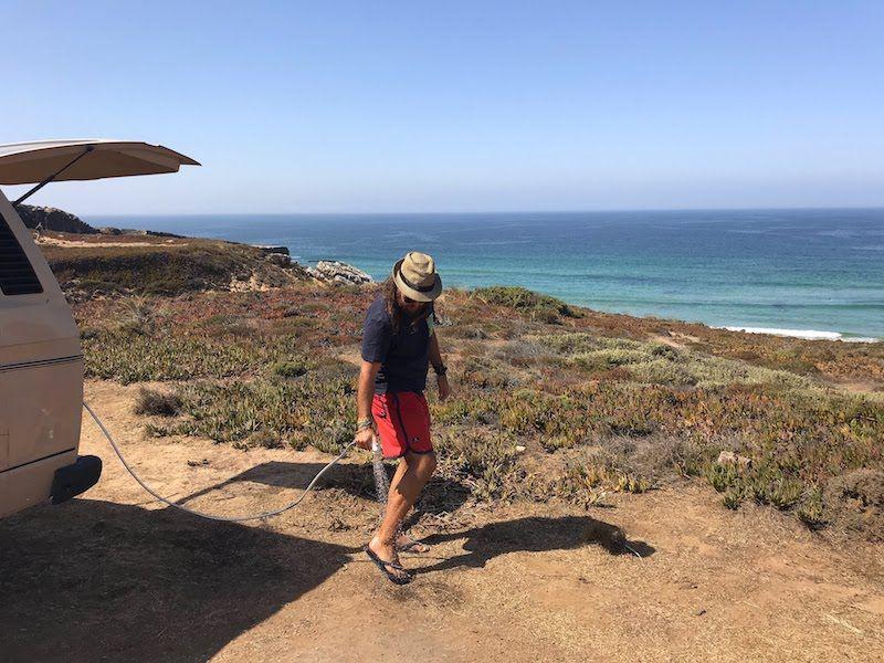 Chris quintando la arena de los pies con la alcachofa de la camper Vanpira, antes de seguir rumbo