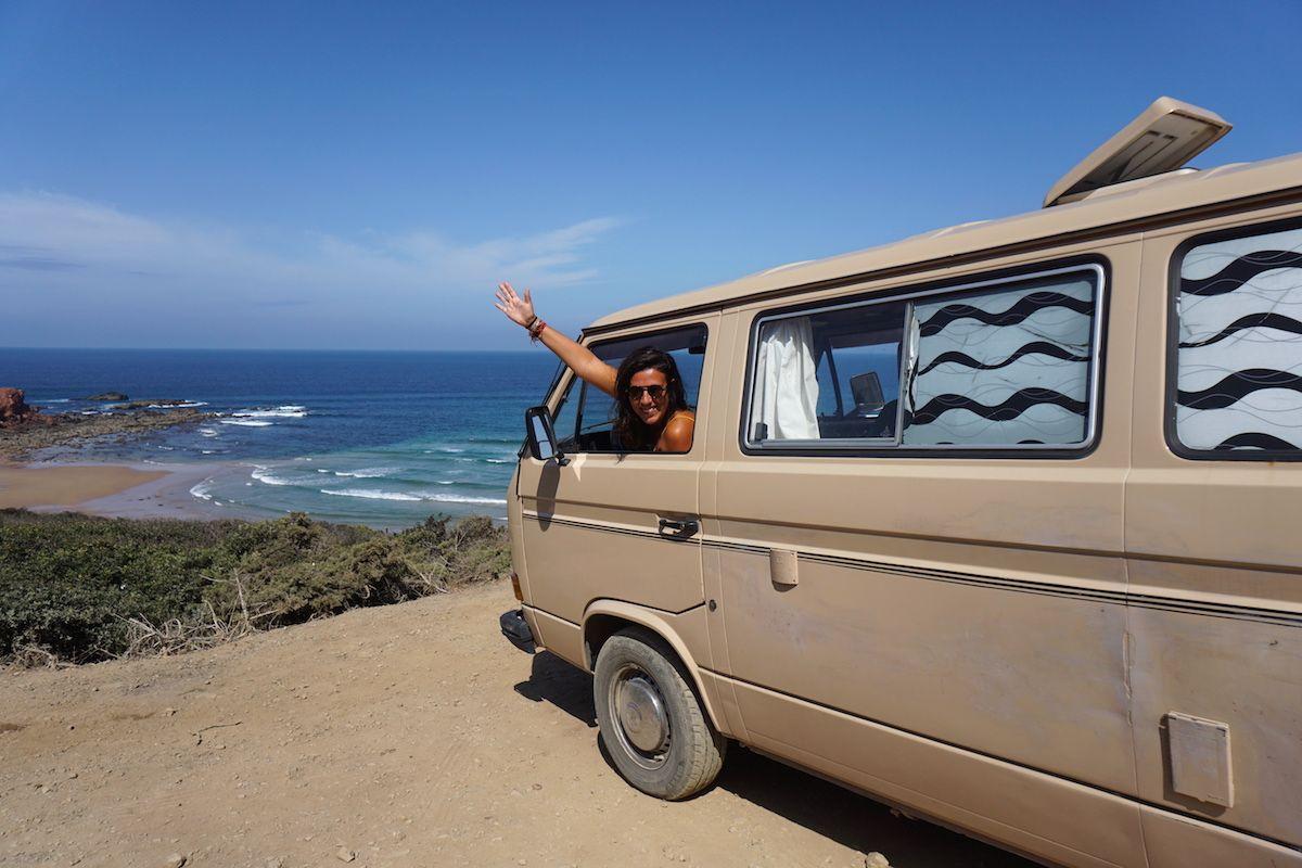 Nuestra camper Vanpira e Inês saludando frente a la bella playa dePonta Ruiva, Sagres