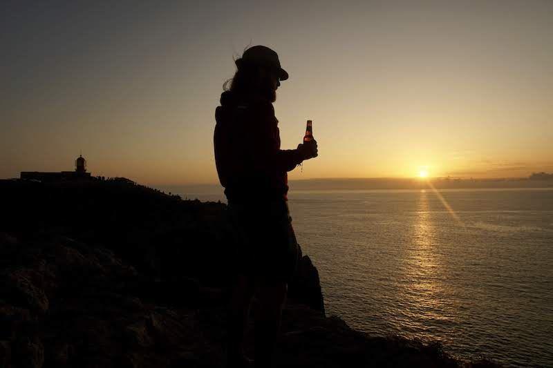 """Chris en """"RandomSunset Beer O'Clock"""" con el faro en el acantilado del cabo de São Vicente"""