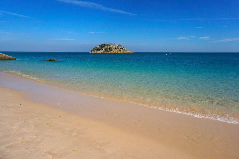 Las aguas cristalinas y la piedra de Anicha en la playa de Creiro