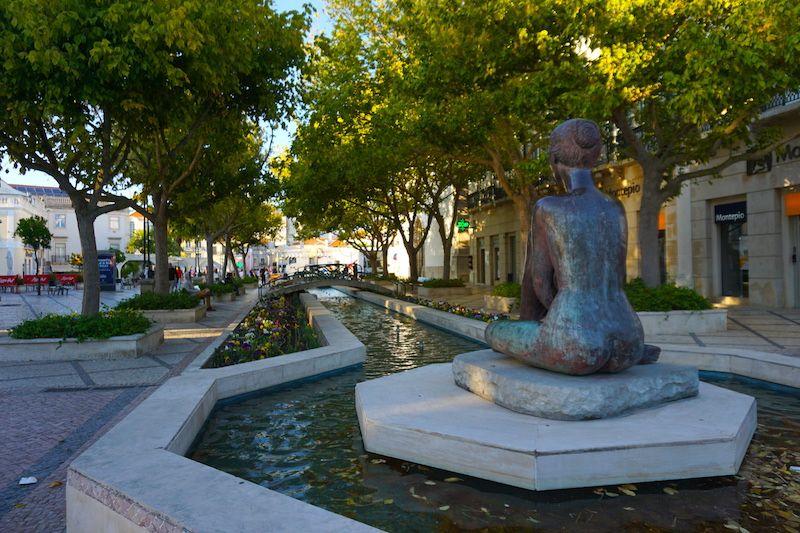 La estatua de Marília, la musa de Bocage, en una extremo de donde de encuentra la estatua del poeta sadino, mirándole.