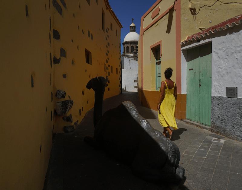 La escultura de bronce del camello de Agüimes con la iglesia de San Sebastián al fondo